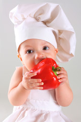 Little baby in a cap chef with Pepper