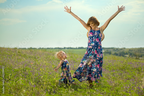Happy mother and daughter standing in field