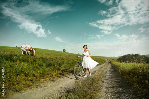 Happy woman on a bike in the countryside.