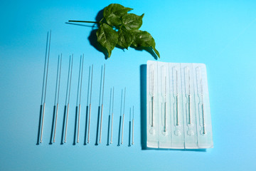 Needles for acupuncture on blue background