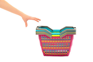 Hand reaching to take a shopping basket from a pile.
