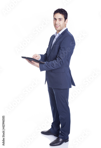 Full body portrait of a handsome business man using a tablet pc,