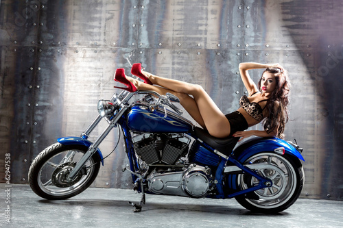 Young sexy woman sitting on motorcycle.