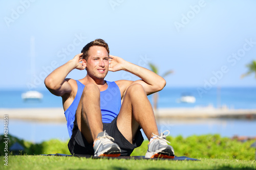 Man exercising sit-ups outside
