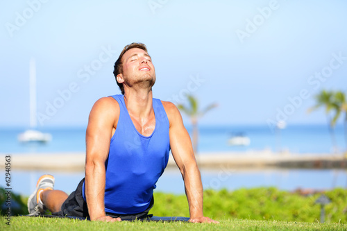 Fitness yoga man in cobra pose stretching abs