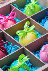 colorful painted easter eggs in a wooden box