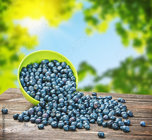 Blueberries в тарелке is scattered on the wooden table