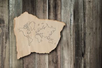 Old paper and world map on grunge wood background