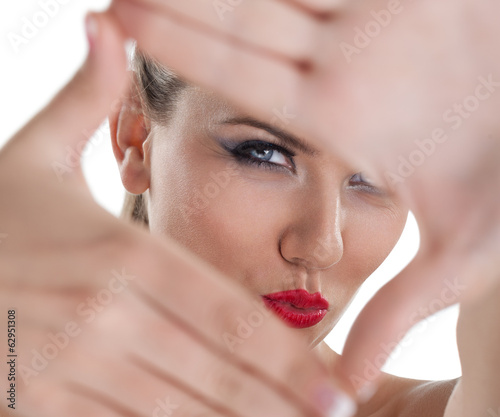 Closeup of young beautiful woman making frame with her hands