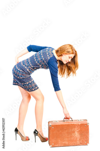fragile slender girl lifts a heavy suitcase