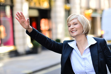 Businesswoman raising her arm to call a taxi