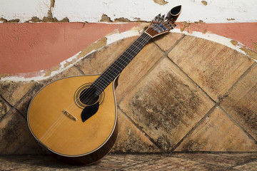 traditional portuguese guitar on a stone bench.