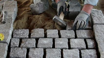 Mason worker making sidewalk pavement with granite blocks