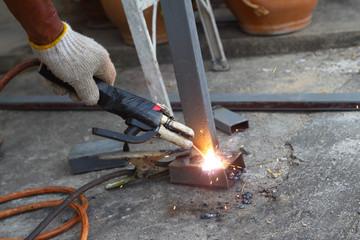 Man hand iron welding  at manufacturing