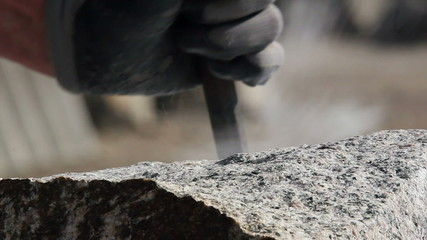 Stonemason making wedge-holes manually