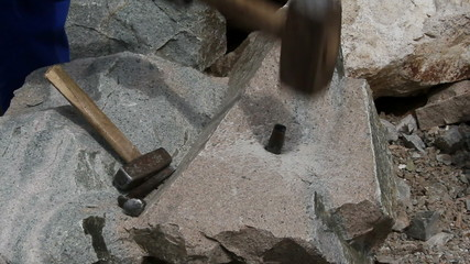 Stonemason cutting a block of granite with wedges and a hammer