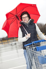 Woman with shopping cart and umbrella