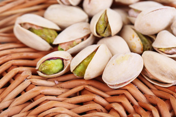 Pistachio nuts on wicker stand close up