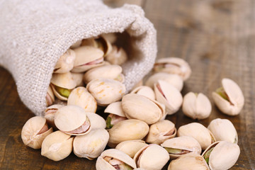 Pistachio nuts in sackcloth bag on wooden background