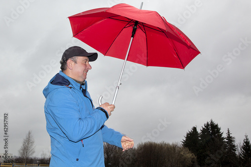Man running with umbrella in rainy stormy weather