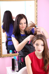 Beautiful woman hairdresser do hairstyle girl in beauty salon