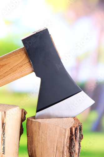 Ax and firewood on nature background