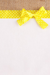 Sackcloth with color ribbon and bow on color fabric background