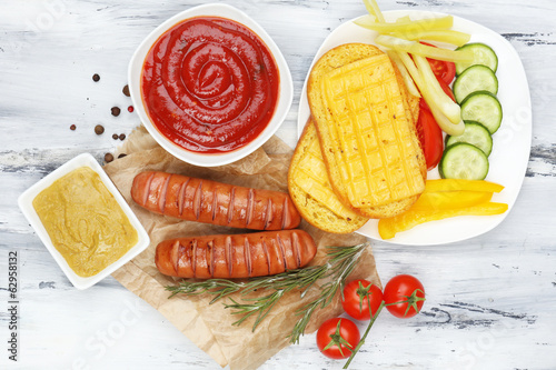 Grilled sausages on wooden table