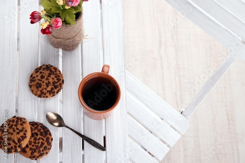 Composition with cup of hot drink and flowers