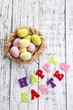 Easter eggs in nest and sign on color wooden background