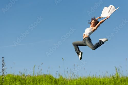 Beautiful young woman jumping on a green grass with a white shir