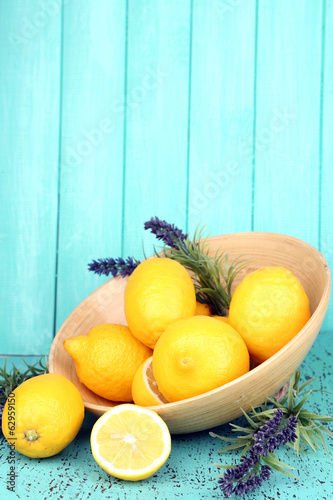 Still life with fresh lemons and lavender on blue background