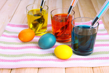 Glasses with paint for Easter eggs and eggs, close up