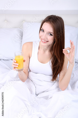 Young beautiful woman with orange juice in bed close-up