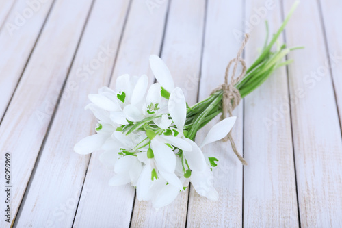 Beautiful bouquets of snowdrops in vases on wooden background