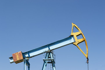 Blue pumpjack on blue sky