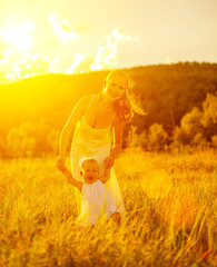 happy family on nature mother and baby doing first steps at suns