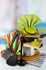 Stacked cooking equipment on wooden table, on light background