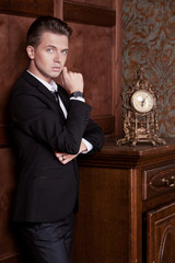 attractive young businessman in a suit in vintage interior