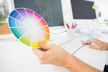 Hand holding color wheel while using computer