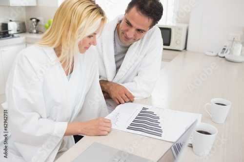 Couple with bills and laptop in kitchen