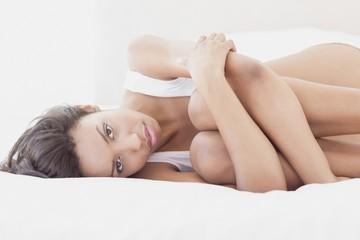 Sad brunette lying on bed hugging her knees