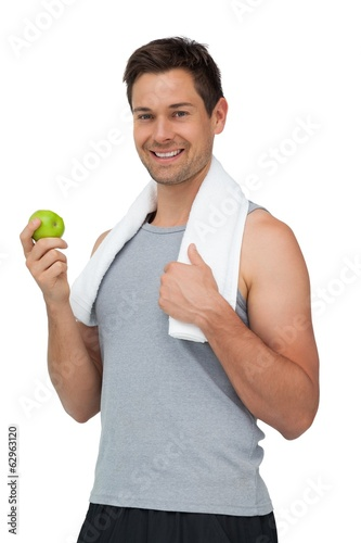 Portrait of a smiling fit young man with apple standing