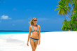 Beautiful bikini model with suntan walking on Maldives
