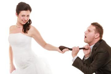 Wedding. Bride pulling tie of groom. Emancipation