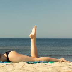 Summer vacation. Legs of sunbathing girl on beach