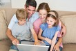 Loving family using laptop together on sofa