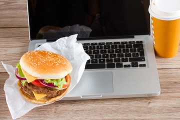 Eating at work place fast food near laptop