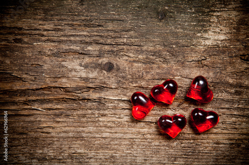 Red glassware hearts on old wooden table