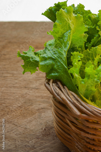 Lettuce in basket on wooden floor.